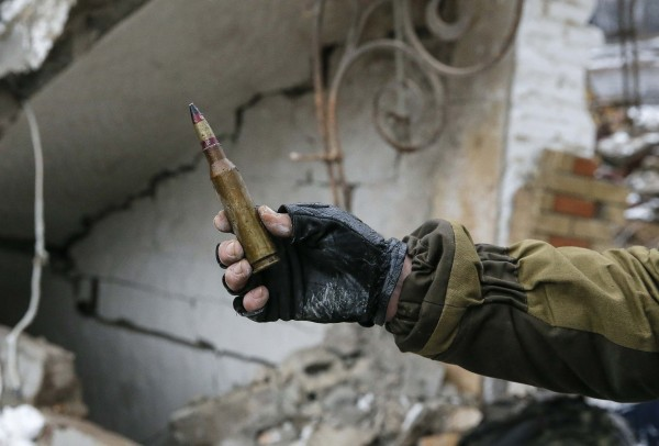 aratist self-proclaimed Donetsk People's Republic holds up a large-caliber bullet for the camera in Vuhlehirsk